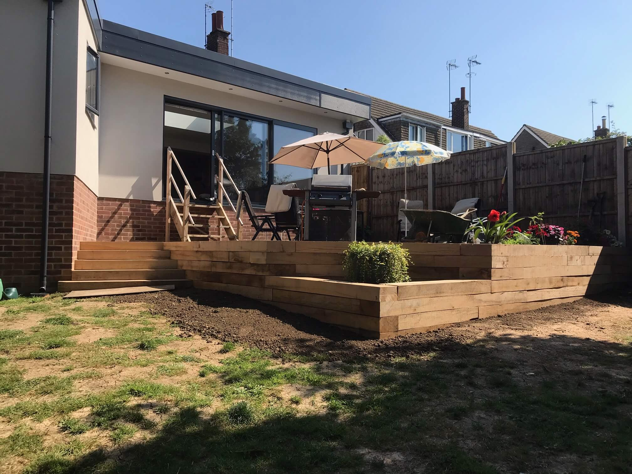 Patio retaining wall with steps built from oak sleepers